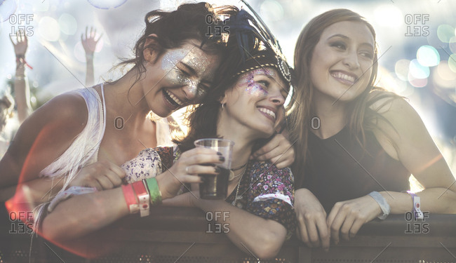 Happy young women drinking at a music festival