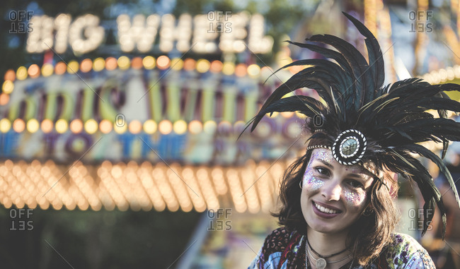 Girl wearing feather headdress in front of a carnival ride