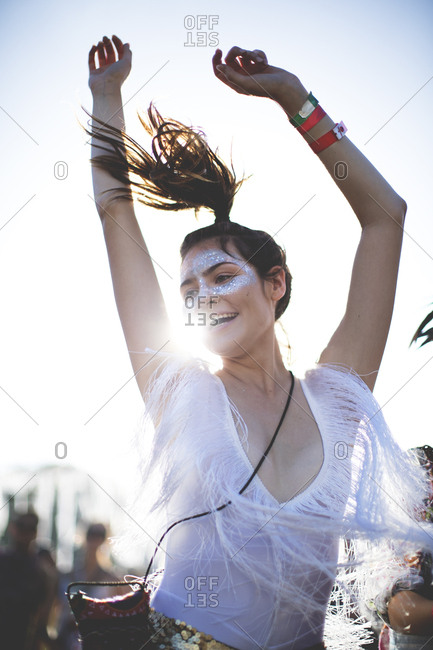 Young woman at a concert waiving her arms in the air
