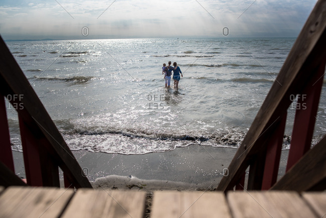 View from lifeguard chair of women and child walking in the surf