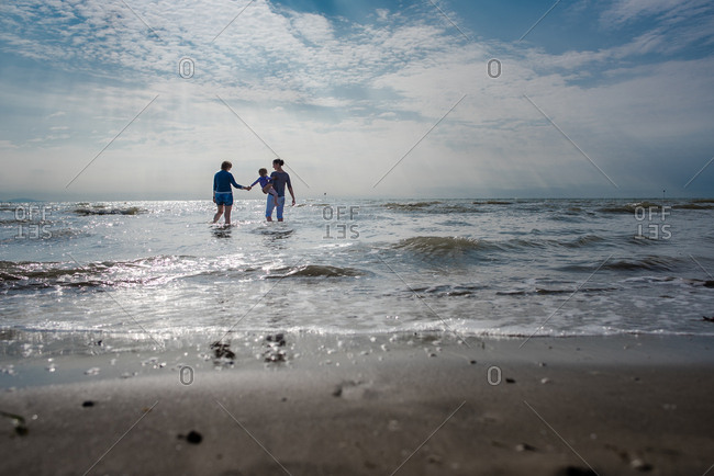 Women and child wade in the surf