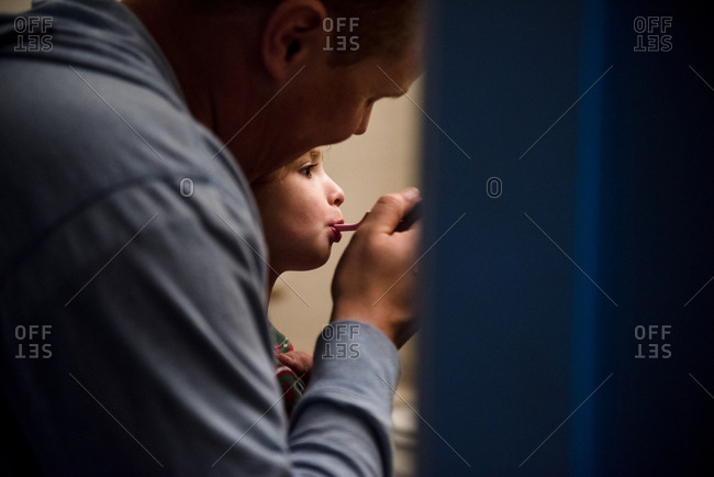 Father brushing his daughter's teeth