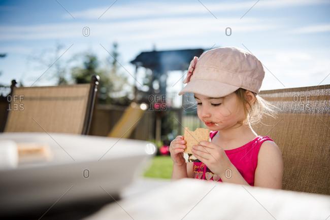Little girl eating s'more in backyard