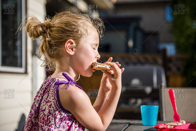 Blonde girl eating s'more in backyard