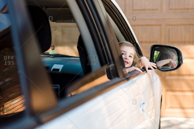 Little girl looking out passenger window of a car