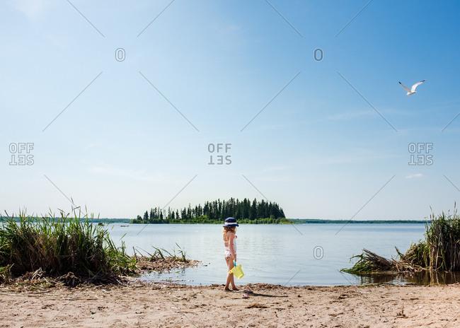 Little girl standing on lakeshore with bucket