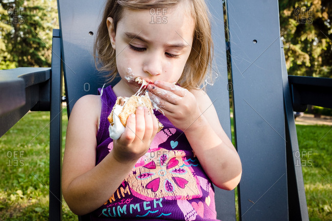 Young girl eating a sticky s'more