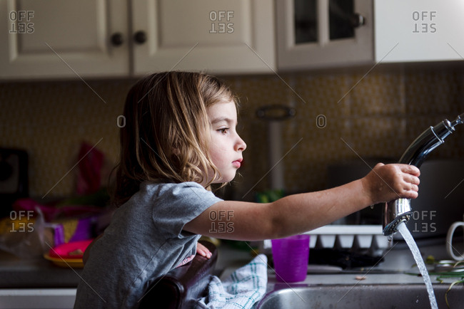 Little girl spraying kitchen faucet