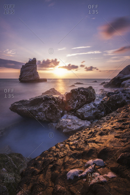 Italy, Marches, Ancona district, Parco del Conero, Portonovo, Mediterranean sea, Adriatic sea, Adriatic Coast, Cliffs and sea framed by the pink sky at sunrise La Vela Beach