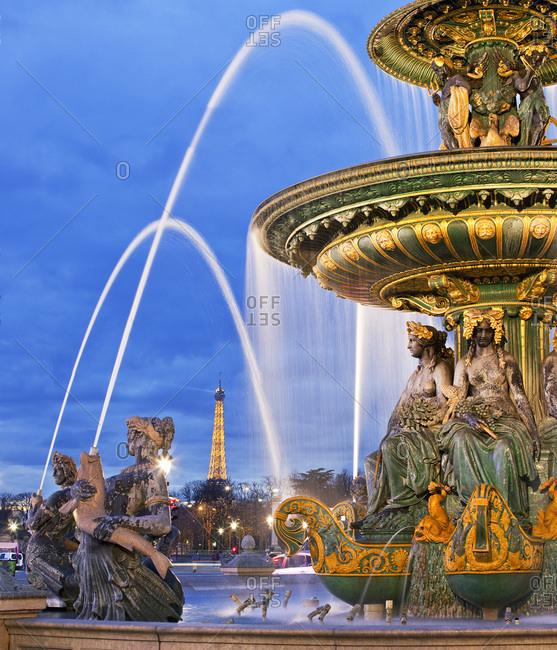 December 13, 2016: France, Ile-de-France, Paris, Champs Elysees, Place de La Concorde, Ville de Paris, Fountain statues and Tour Eiffel in the background