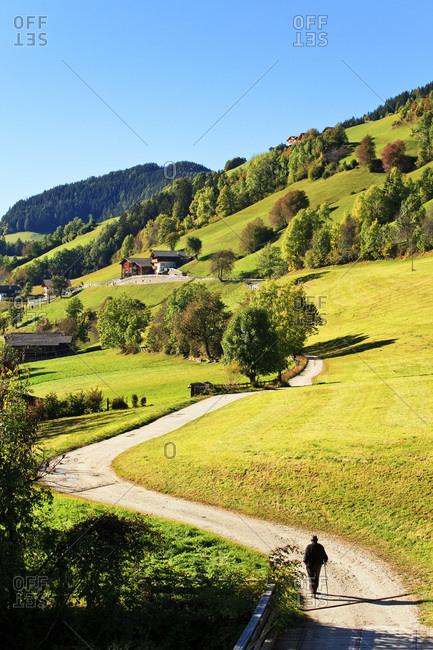Italy, Trentino-Alto Adige, Bolzano district, South Tyrol, Val di Funes, Santa Maddalena, Alps, Dolomites, Old man walking on a white road