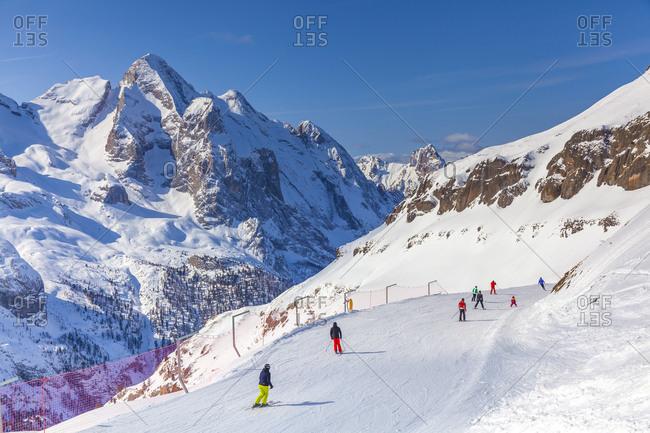 Italy, Veneto, Belluno district, Alto Agordino, Arabba, Alps, Dolomites, Porta Vescovo, skiers, Gran Vernel and Colac mountains