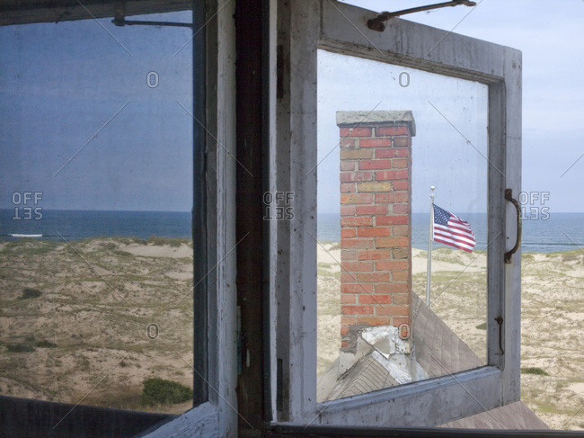 Windows on a beach house with chimney and American flag
