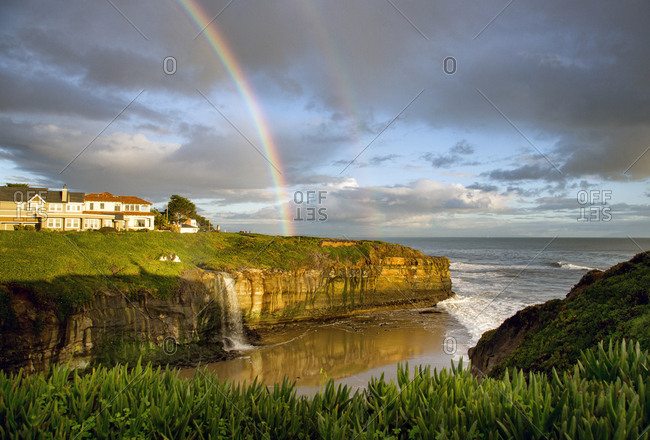 Rainbow over cliff with waterfall in Santa Cruz, California