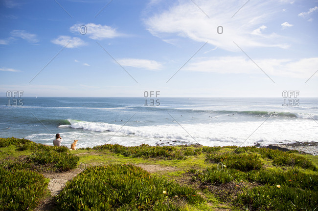 Woman overlooking waves and surfers from the coast of Santa Cruz, California