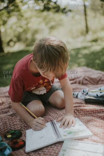 Boy drawing a picture in a sketch pad