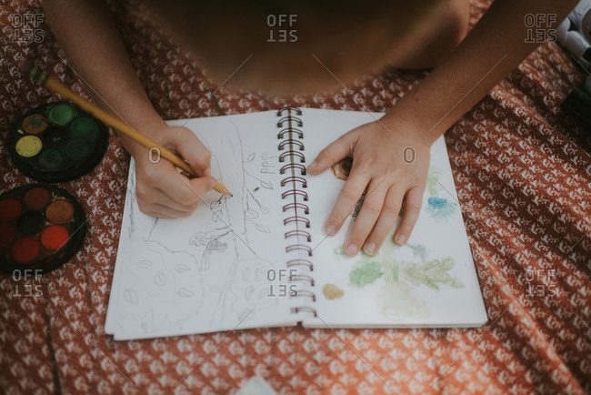 Boy drawing a picture of a tree in a sketch pad