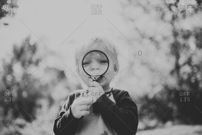 Toddler boy looking through magnifying glass in black and white