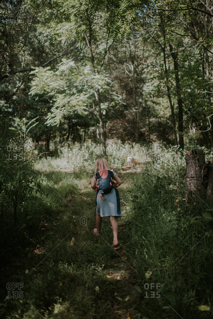 Blonde girl carrying baby doll on a nature trail