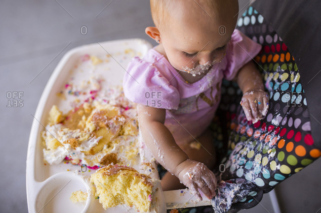 High angle view of baby girl playing with food while sitting on high chair at home