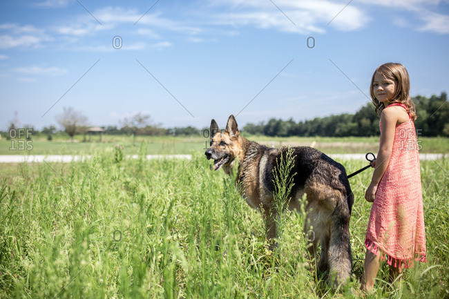 Portrait of girl with German Shepherd standing on field during sunny day against sky