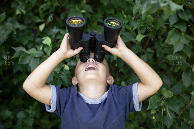 Playful boy looking through binoculars while standing against plants