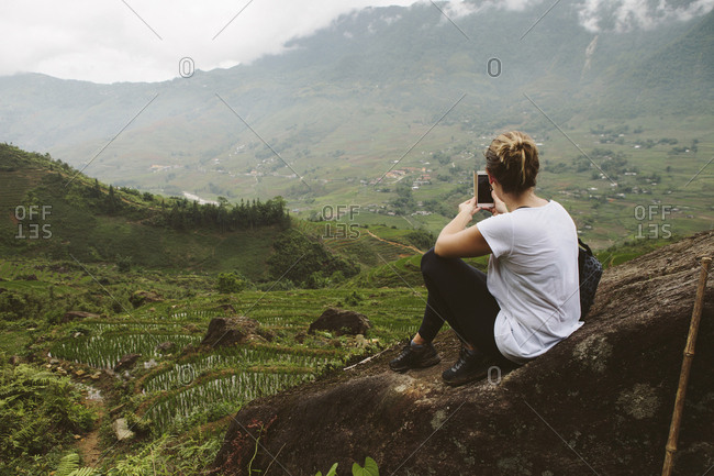Rear view of woman photographing landscape with smart phone
