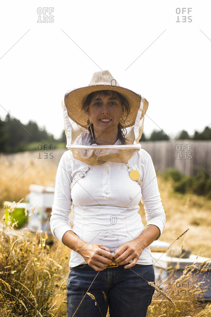 Portrait of beekeeper wearing protective mask and hat while standing on field against clear sky