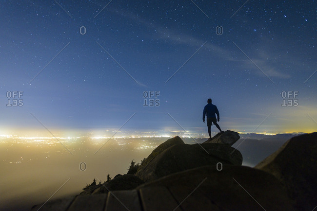 Silhouette man standing on rocks against star field at Mount Pilchuck State Park during night