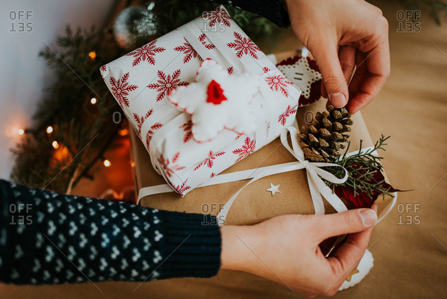 Person decorating wrapped Christmas presents with pine cones and felt Christmas ornaments