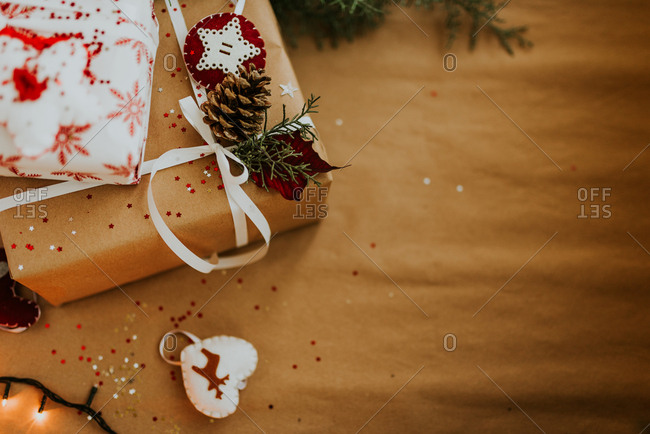 Christmas presents wrapped in ordinary and white paper and decorated with white ribbon, pine cone, and star felt ornament