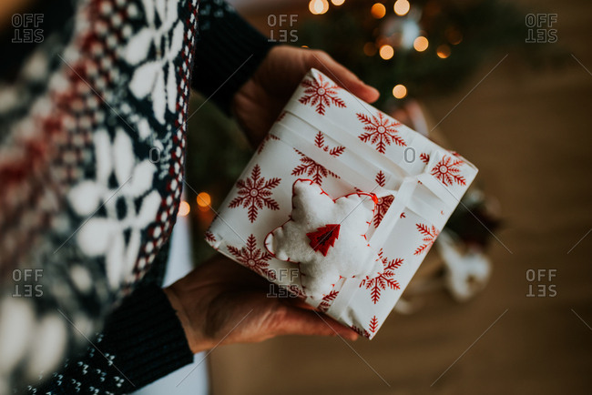 Person holding Christmas present wrapped in white paper with red snowflakes and decorated with star felt ornament