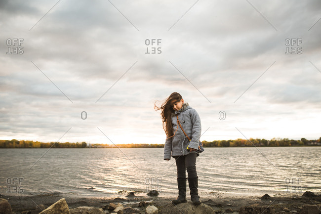 Girl standing on a rock along shore of bay