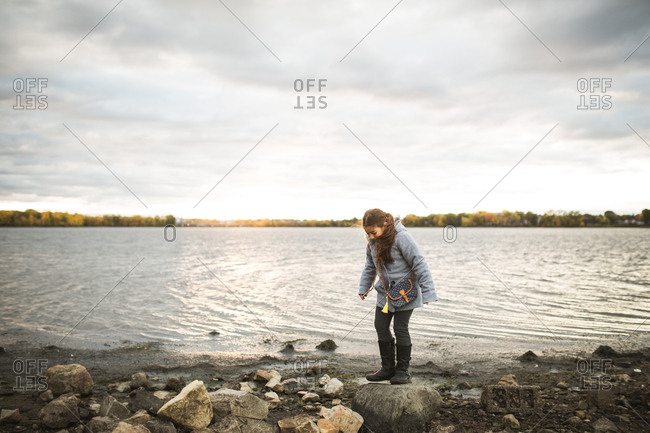 Girl walking on rocks along shore of bay