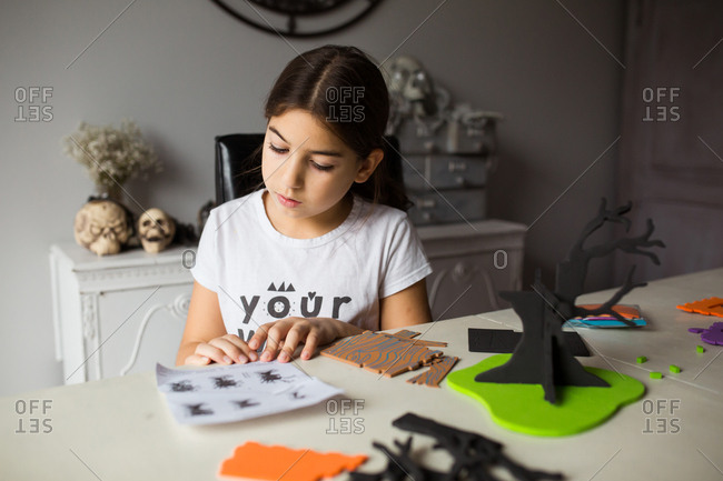 Girl following instructions to make a Halloween craft