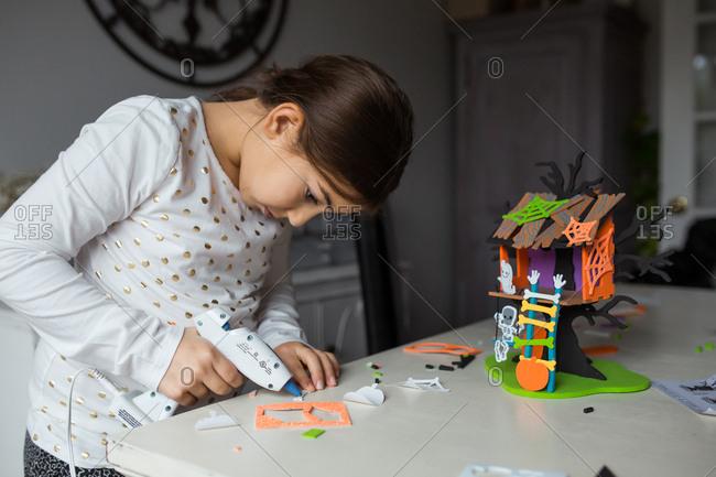 Girl using a glue gun to assemble a Halloween craft