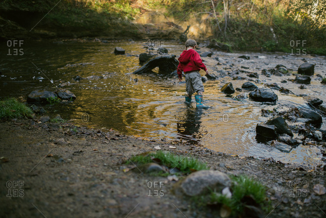 Boy wading among rocks in creek