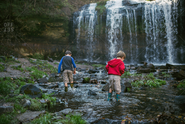 Children wading in creek near waterfall