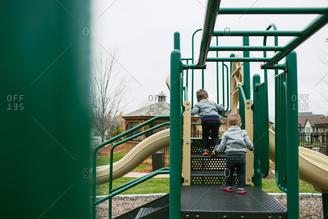 Children climbing stairs on playground equipment