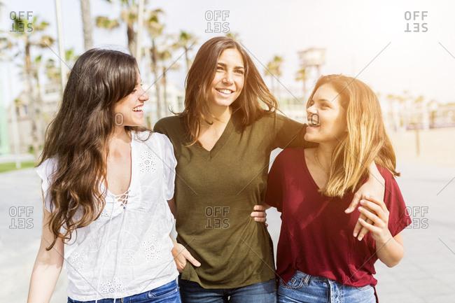 Three happy female friends strolling on the boardwalk