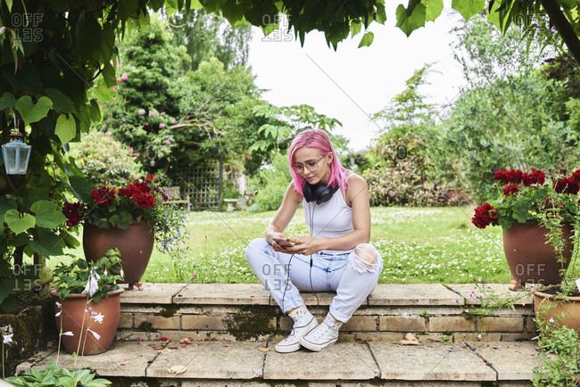 Young woman with pink hair wearing headphones and using cell phone in garden