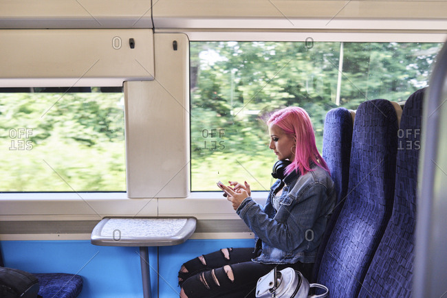 Young woman with pink hair using cell phone while traveling by train