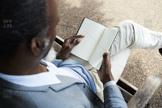 Man reading on bench in a park- partial view