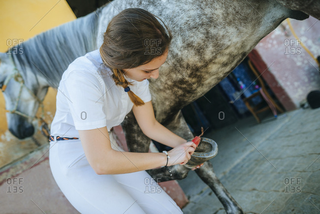 Young woman cleaning hoof of horse