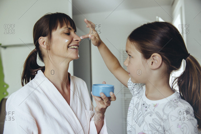 Daughter putting facial cream on mother's face
