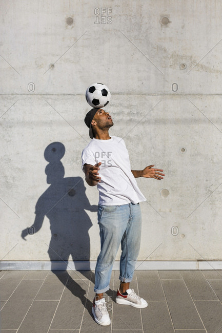 Young man balancing soccer ball on his head in front of concrete wall