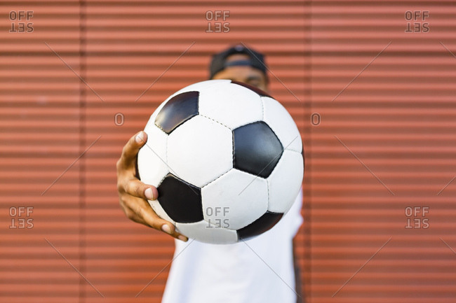 Man's hand holding soccer- close-up
