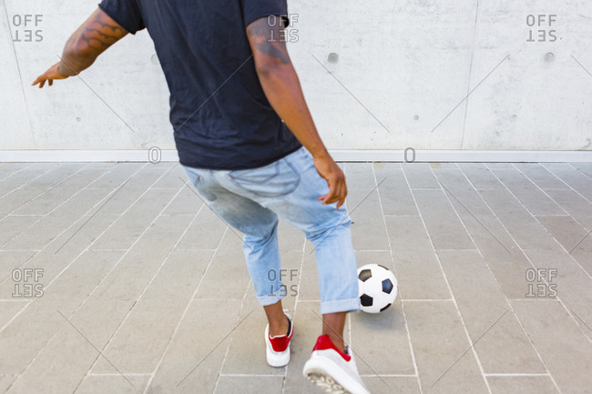 Back view of young man playing with a soccer ball against concrete wall- partial view