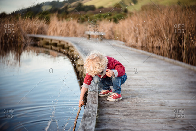 Boy splashing water with stick