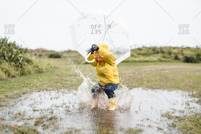 Boy splashing in puddle with umbrella